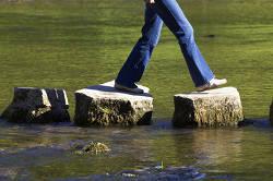 Eine Frau geht über Felsbrocken im Wasser.